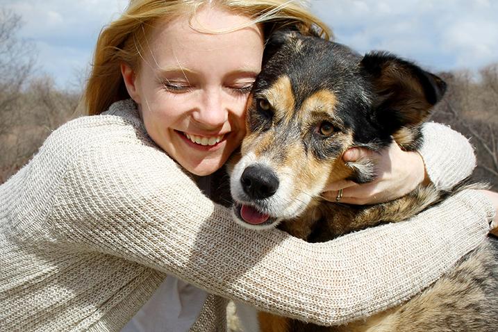 woman hugging a shepherd dog